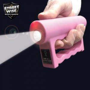 pink brass knuckle stun gun flashlight in dark